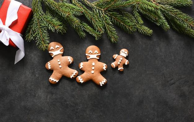 마스크에 진저 브레드 가족입니다. 진저 쿠키와 선물 크리스마스 배경입니다. 프리미엄 사진