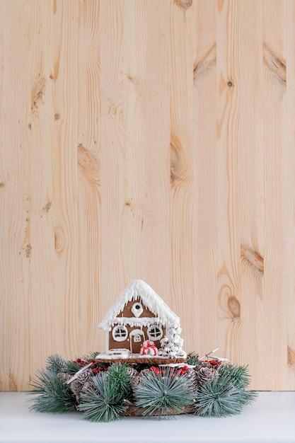 明るい木の背景にジンジャーブレッドの家とクリスマスリース。スペースをコピーします。 Premium写真