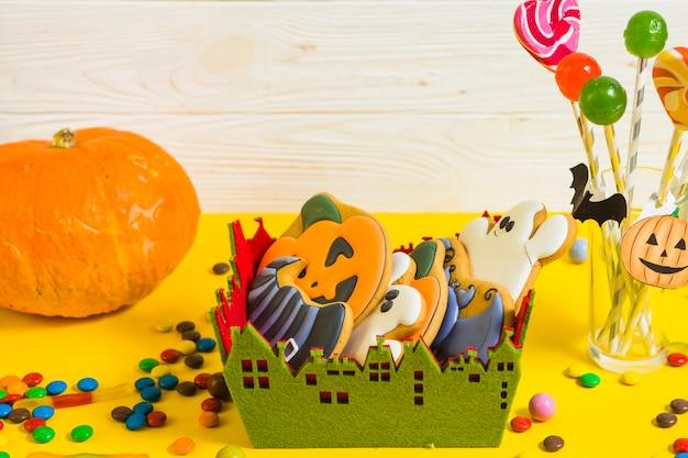 Gingerbread in little box near pumpkin and lollipop Free Photo