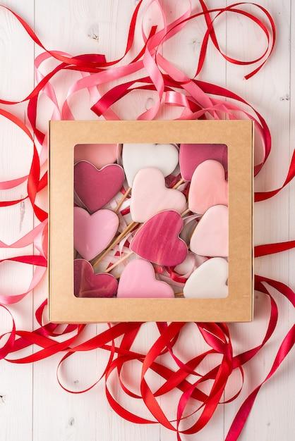 ギフトボックスライトテーブルのハートの形をした棒にジンジャーブレッド。バレンタイン・デー。 Premium写真