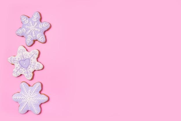 Пряники звезды снежинки на сладком розовом фоне. вид сверху. Premium Фотографии