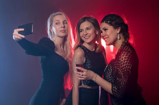 Подружки на вечеринке, принимая селфи Бесплатные Фотографии