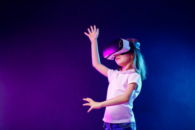 Girl 7 y.o. experiencing vr headset game on colorful . child using a gaming gadget for virtual reality. Premium Photo