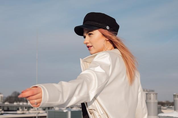 가벼운 비옷과 모자에 푸른 봄 하늘을 배경으로 소녀가 기대에 손을 뻗어 있습니다. 프리미엄 사진