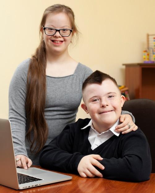 Девочка и мальчик с синдромом дауна позируют счастливо Бесплатные Фотографии