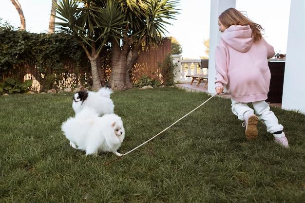 Девочка и милые белые щенки играют в саду Бесплатные Фотографии