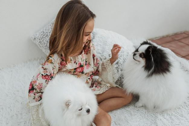 Девушка и милые белые щенки сидят на кровати Бесплатные Фотографии