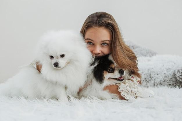 ベッドに座っている女の子とかわいい白い子犬 無料写真