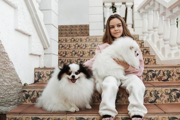 Девушка и милые белые щенки сидят на лестнице Бесплатные Фотографии