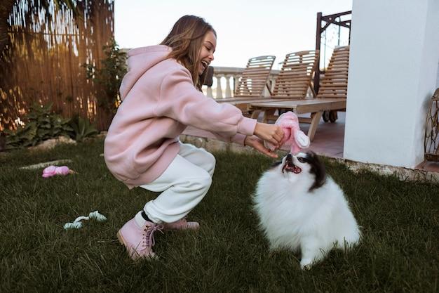 Девушка и собака, играя на открытом воздухе Бесплатные Фотографии