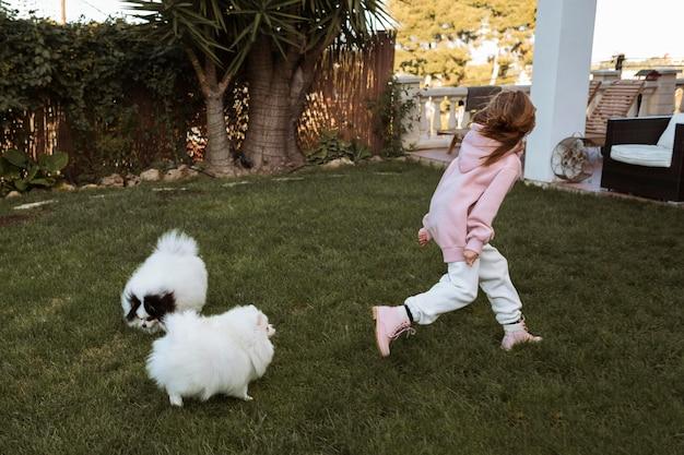 Девушка и собаки бегают и играют Бесплатные Фотографии