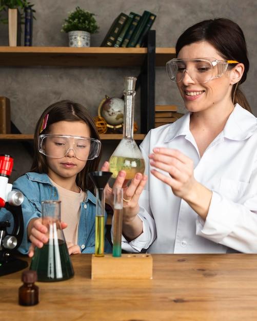 시험관으로 과학 실험을하는 소녀와 여성 교사 무료 사진