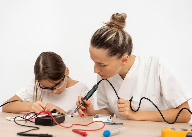 科学実験をしている女の子と女性の先生 無料写真