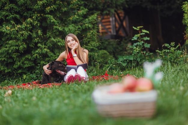 庭に座っている女の子と彼女の犬。 Premium写真