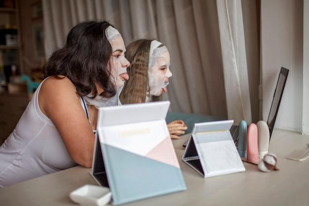 スパの手順中にガジェットを使用している女の子と彼女の母親、インターネットを介してチャットしているママと娘 Premium写真