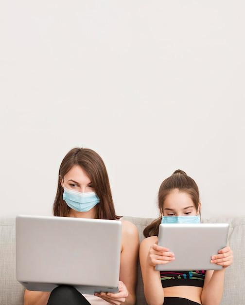 Девочка и мама на диване с электронным устройством Бесплатные Фотографии