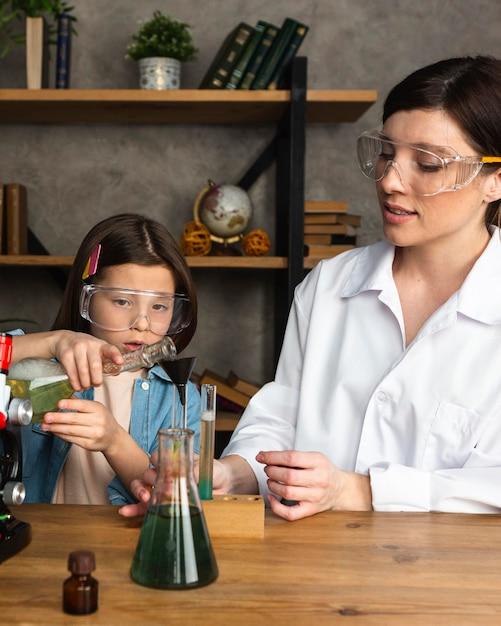 소녀와 교사 시험관으로 과학 실험을하고 무료 사진