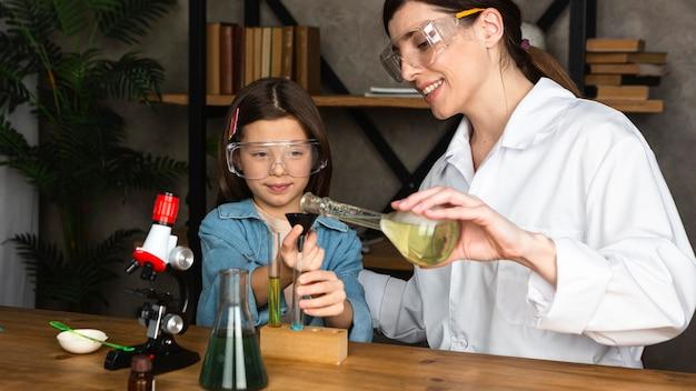 소녀와 과학 실험을하는 교사 무료 사진