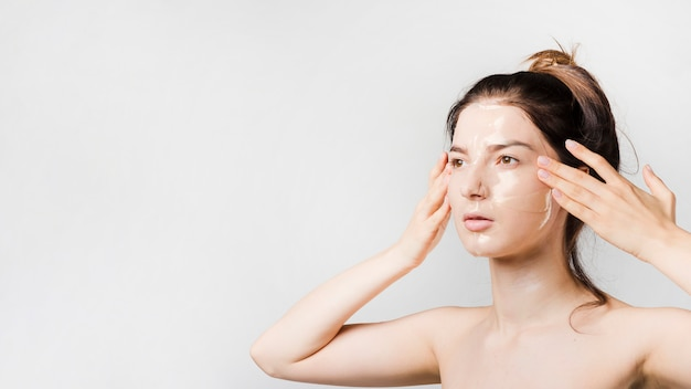 Girl applying herself cosmetic product Free Photo