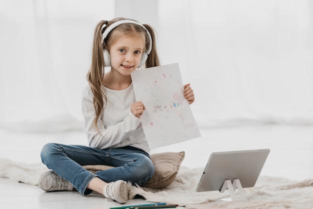 Девушка посещает виртуальные классы и держит рисунок Бесплатные Фотографии
