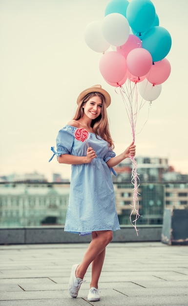 The girl in a beautiful dress holds balloons. Premium Photo