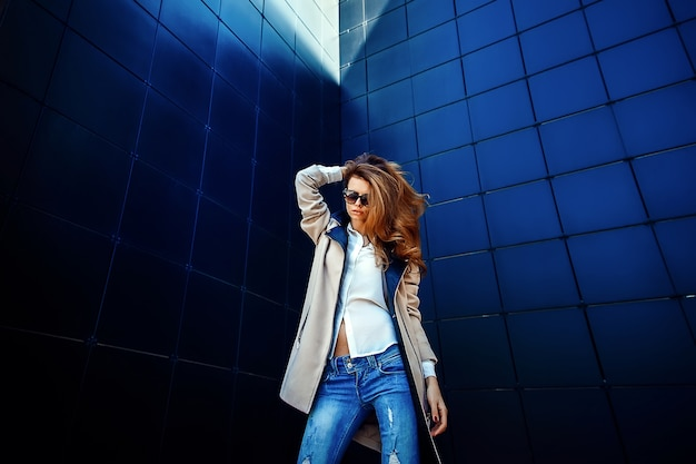 Girl in a beige coat and blue jeans Premium Photo