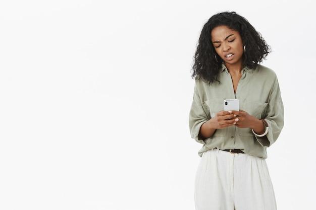 Ragazza che è scontenta tenendo lo smartphone guardando con disgusto Foto Gratuite