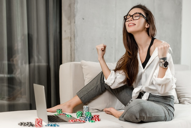 Girl betting and playing poker online on laptop, winning money in casino Premium Photo