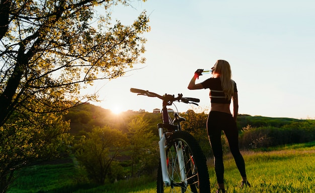 Girl bicyclist drinks clean water after training near her bicycle in the rays of the rising sun Premium Photo