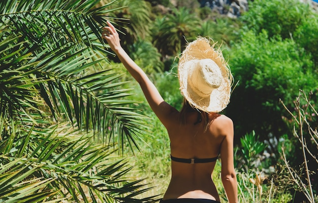 Girl in bikini and hat have rest in palm forest Premium Photo