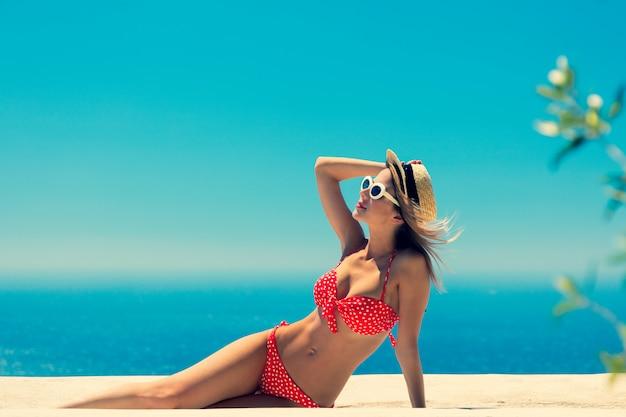 Girl in bikini with blue sea and sky on background Premium Photo