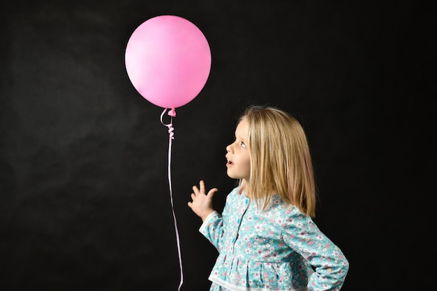 The girl on a black background blows a balloon Premium Photo