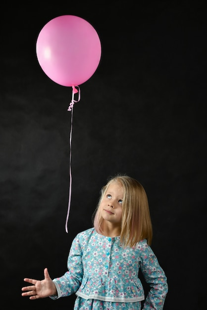 The girl on a black background blows a balloon Premium Photo