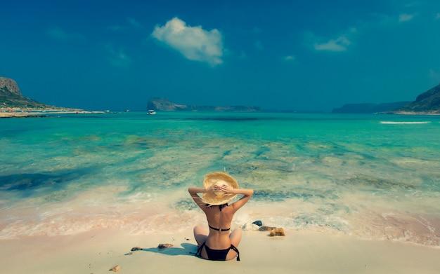 Girl in black bikini and with hat on balos beach Premium Photo