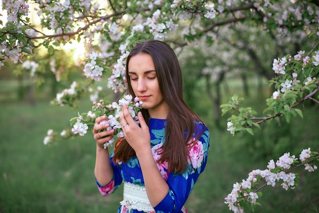 Girl in a blooming apple orchard at sunset Premium Photo
