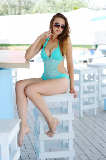 Girl in a blue bathing suit and sunglasses at the resort Premium Photo