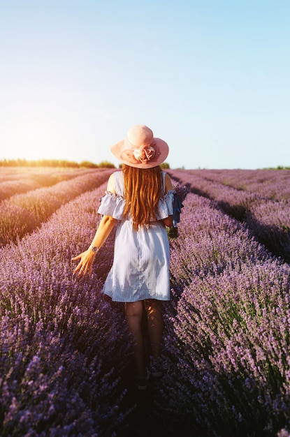A girl in blue dress walking trough lavender fields at sunset. Premium Photo