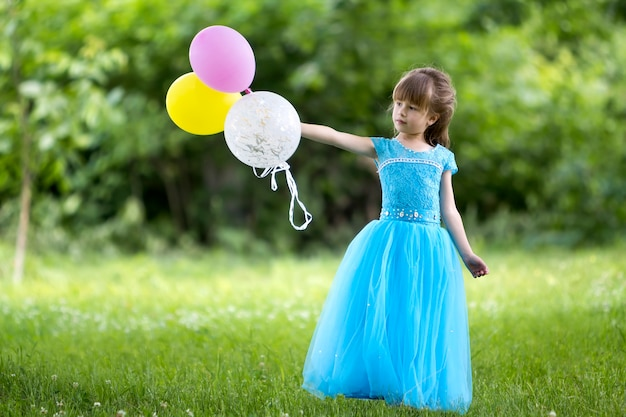 Girl in blue evening dress holding colorful balloons Premium Photo