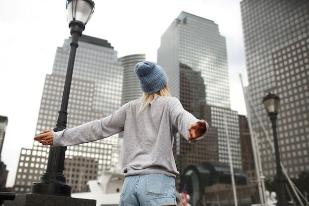 Girl in blue hat and grey sweater stands on the street with skyscrapers Free Photo