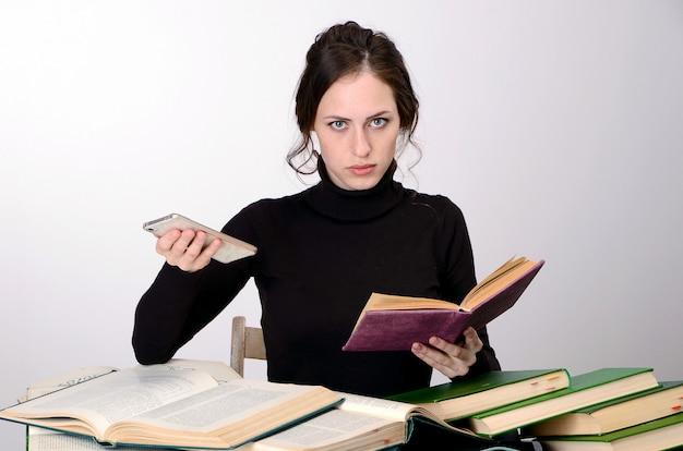 Девушка книги экзамен черный свитер трудности учит за столом усталый радуется эмоции Premium Фотографии