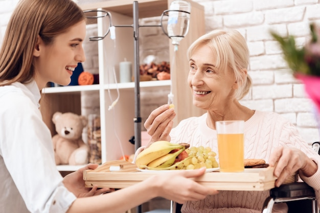Girl brings breakfast woman is eating fruit Premium Photo