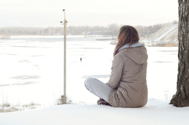 Girl in a brown coat staring into the horizon line between the sky and the frozen lake in winter Premium Photo