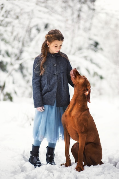 Girl and brown dog in nature in winter Premium Photo