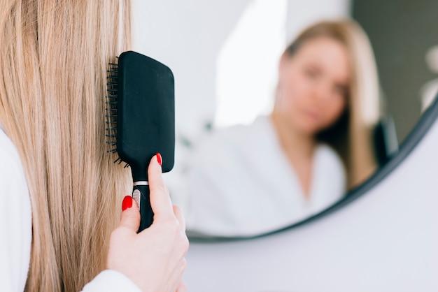 Girl brushing her hair at the bathroom Premium Photo