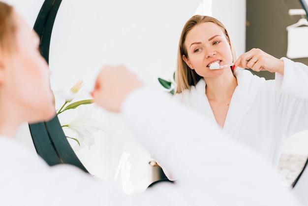 Girl brushing her teeth at the bathroom Free Photo