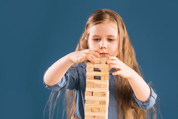 Girl building jenga tower Free Photo