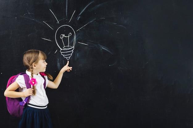Girl at bulb on blackboard Premium Photo