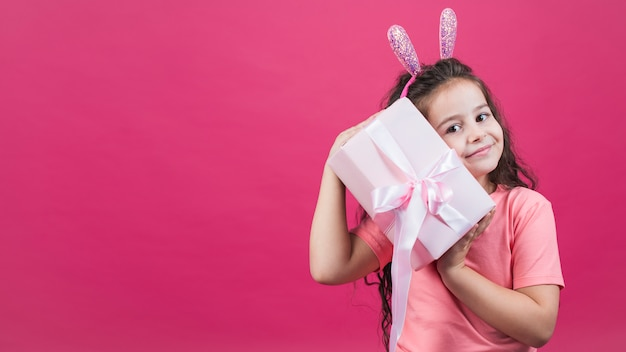 Girl in bunny ears holding gift box Free Photo