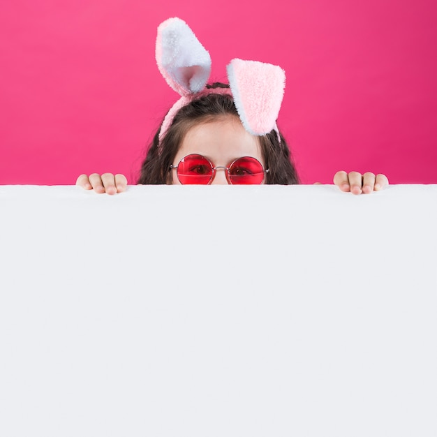 Girl in bunny ears and sunglasses hiding behind table Free Photo