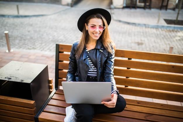 女の子のビジネス女性は秋の公園の街の木製のベンチに座る 無料写真